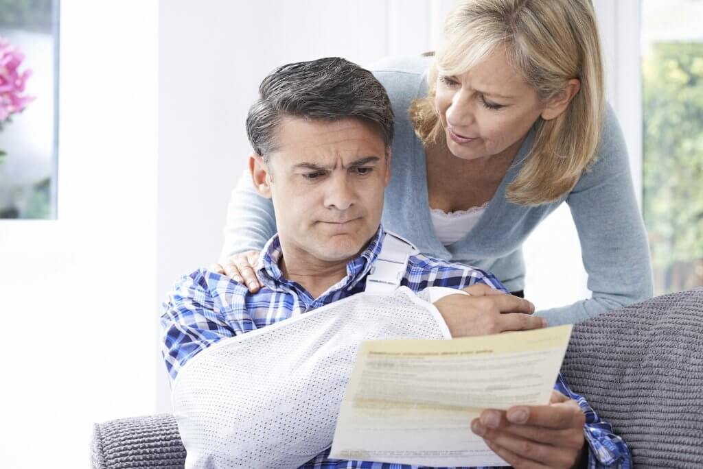 Man with injured arm looking at medical bills with wife