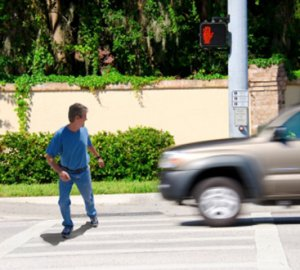 man walking at cross walk missing oncoming car