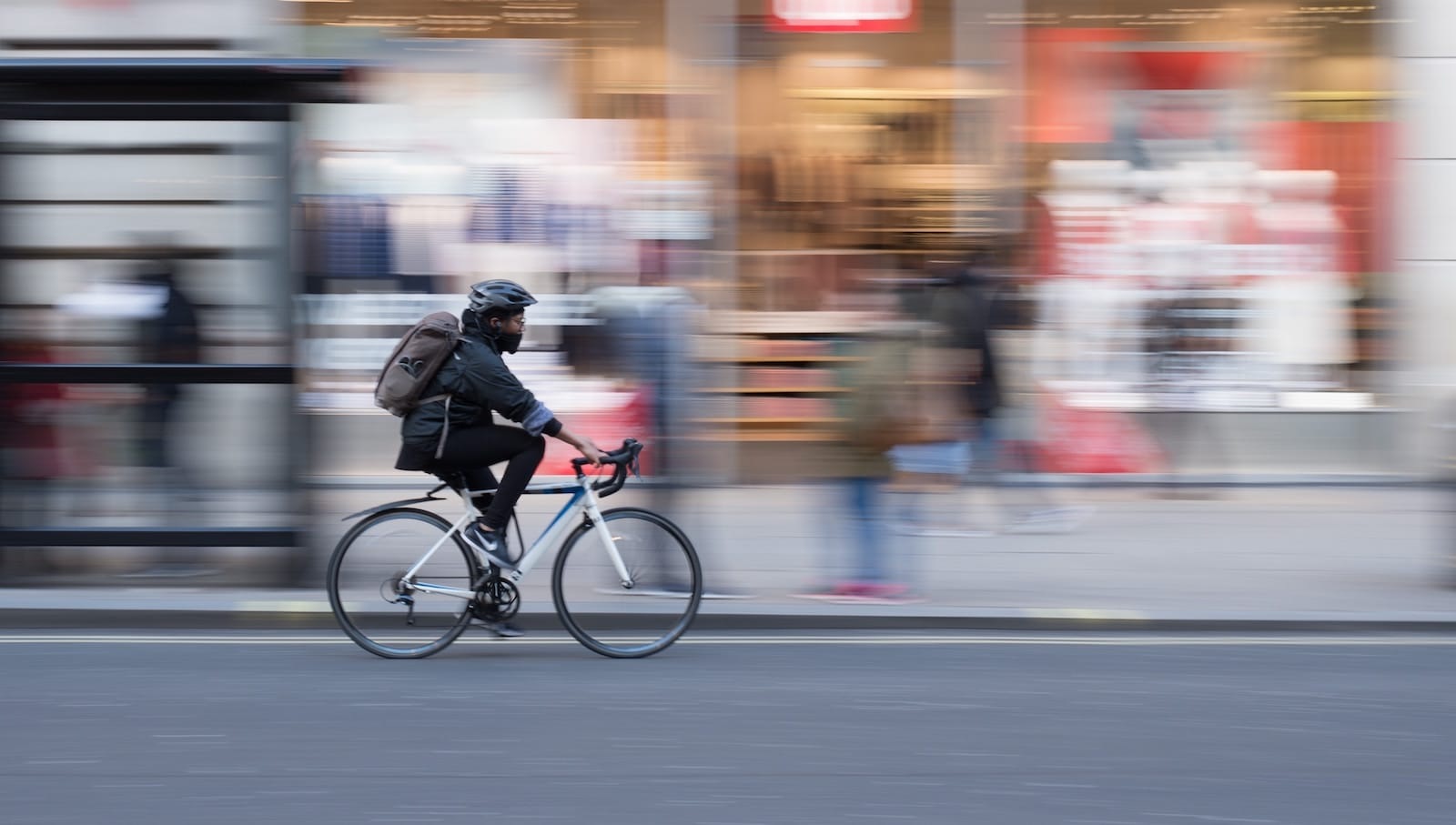 person bicycling in city blurred