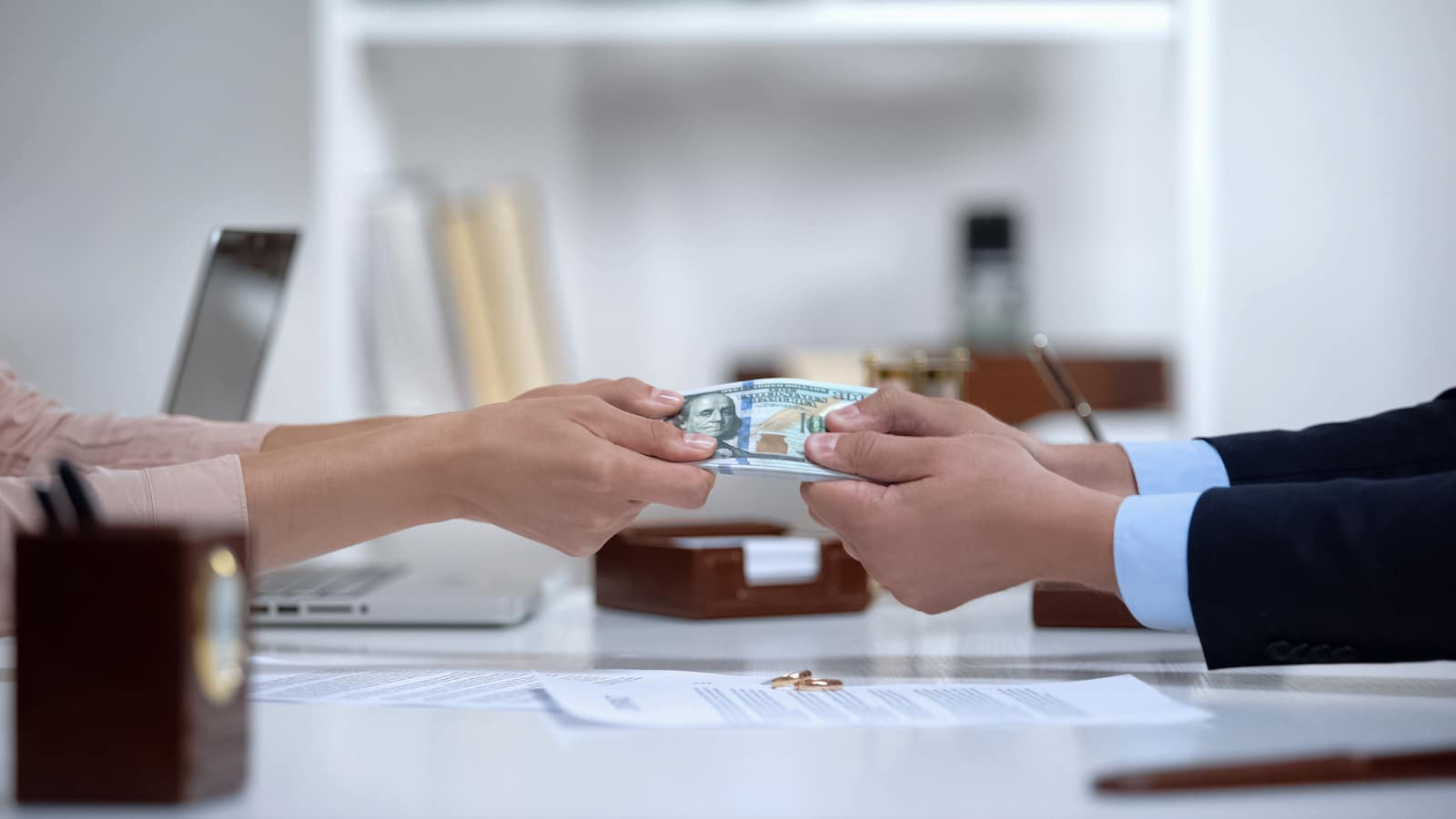 Male and female hands pulling money, dividing marital property during divorce