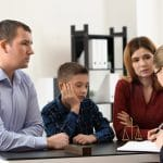 Divorced parents with their son visiting lawyer. Concept of child support
