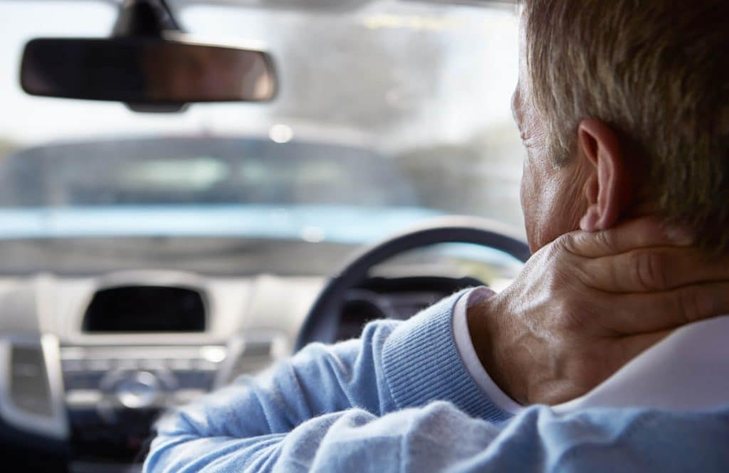 Man inside car holding neck after accident