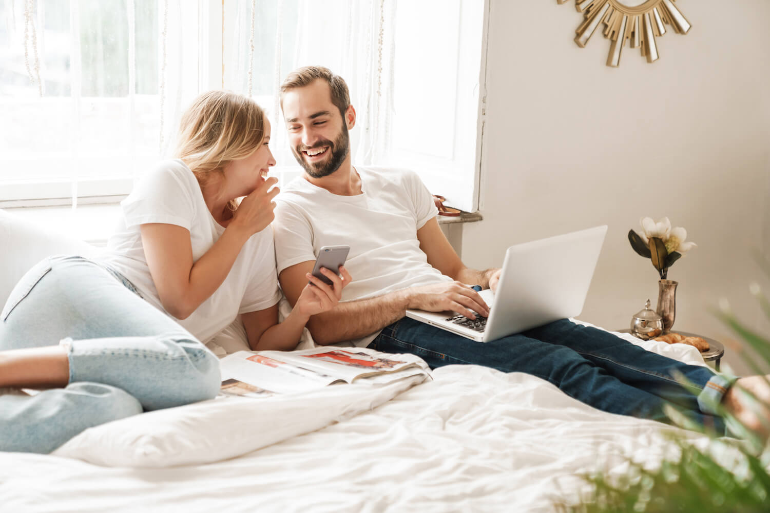 Couple sitting on bed with laptop smiling at each other