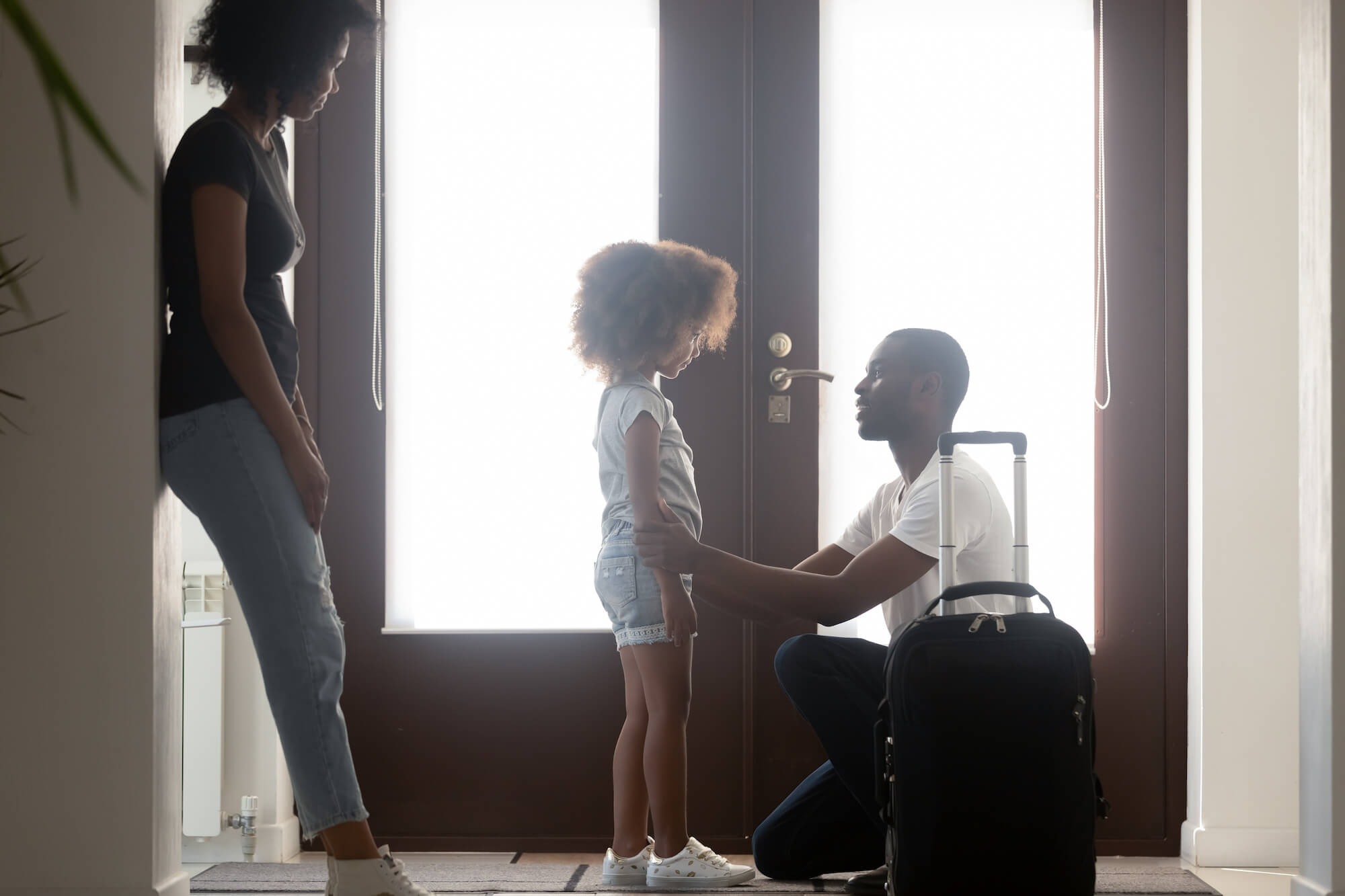 Father kneeling talking to daughter before leaving her with mother