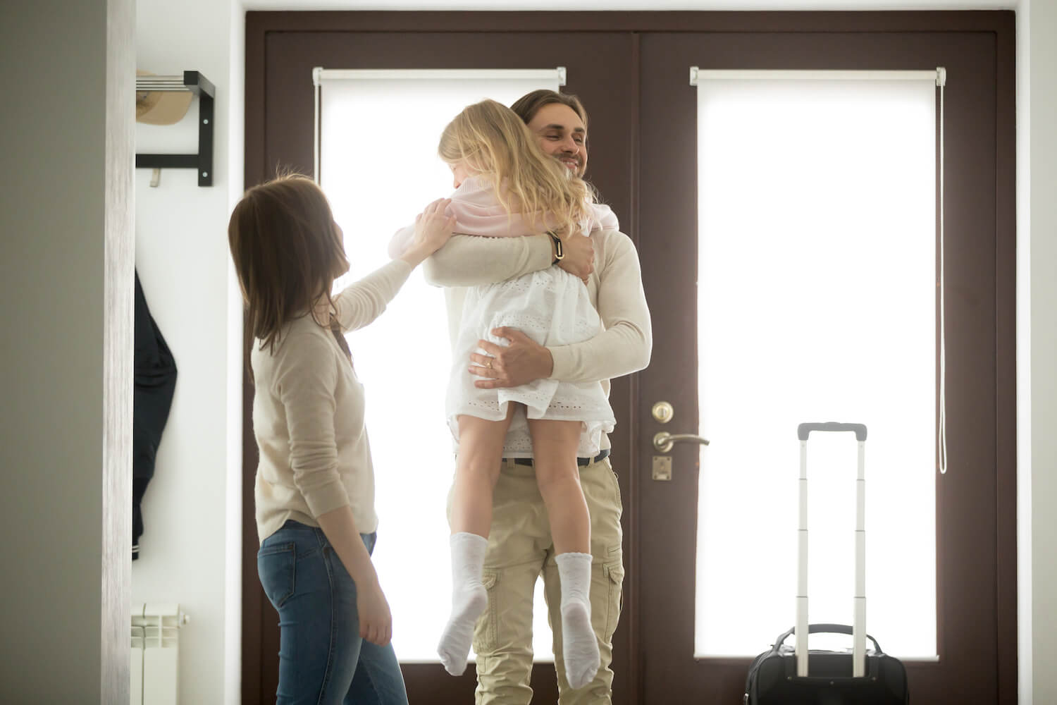 Happy father hugging little daughter arriving returning after trip away