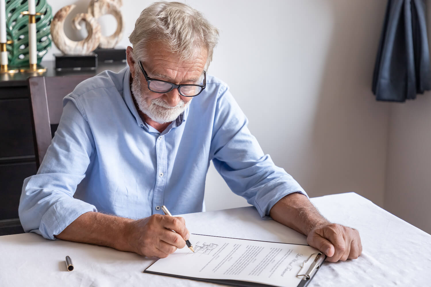 Elderly man with glasses signing a legal document