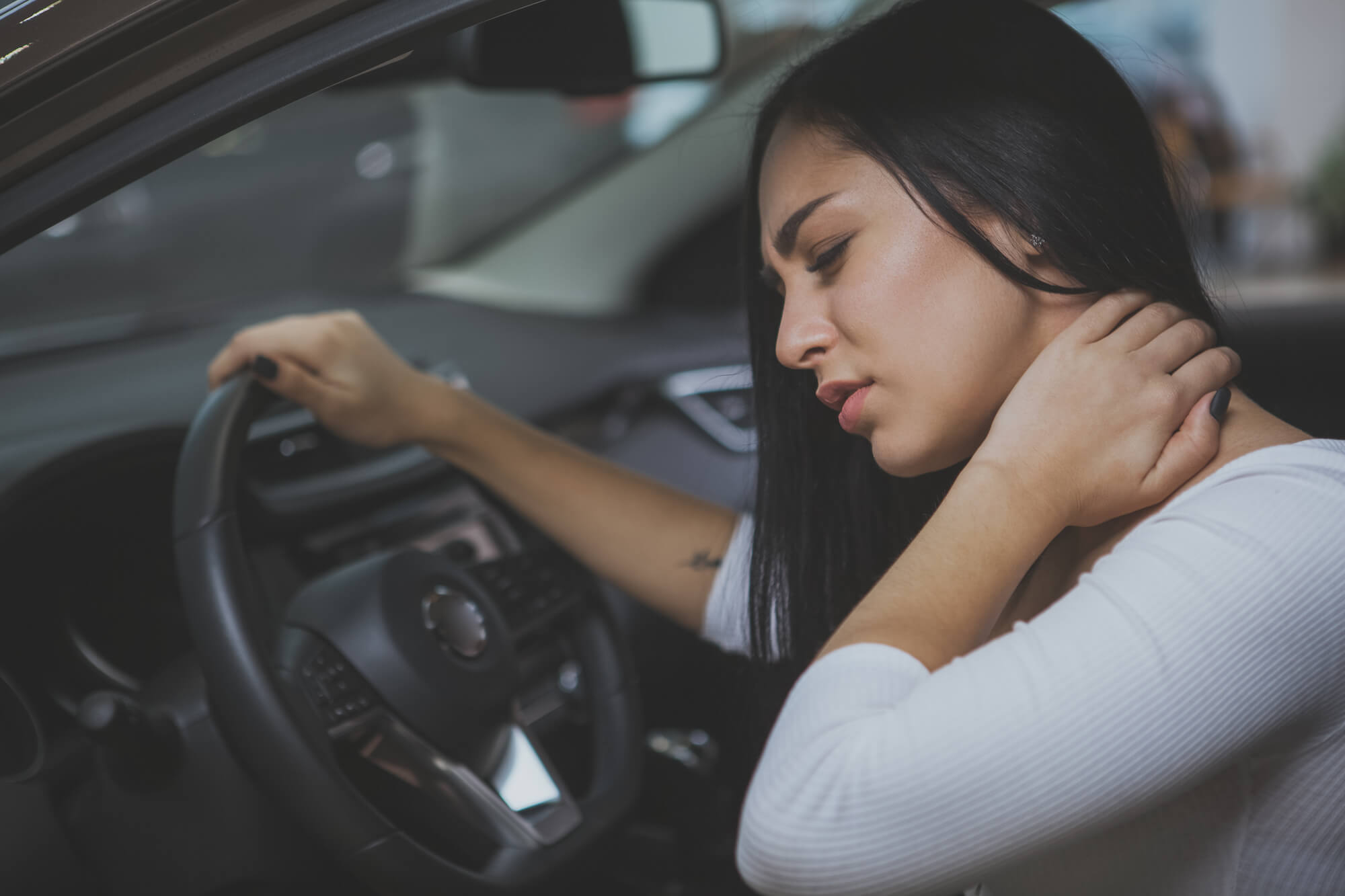 Young woman in vehicle holding back of her neck in discomfort